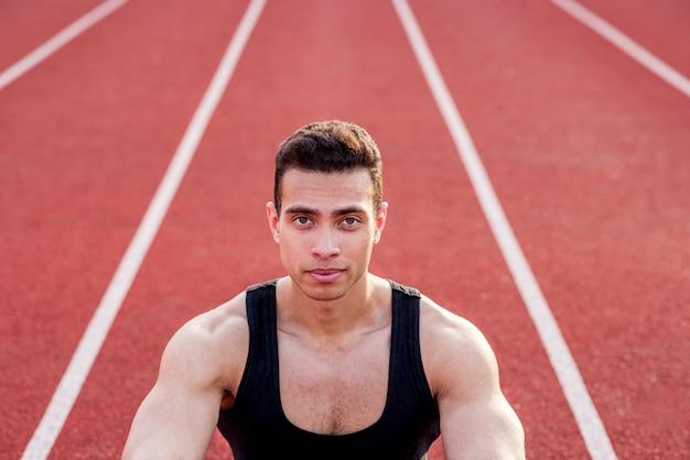 Persona sicura dello sport muscolare sulla pista di corsa rossa che esamina macchina fotografica