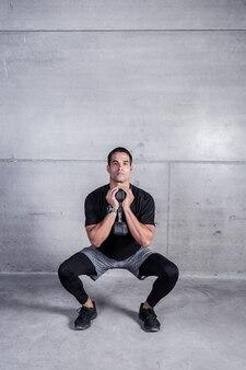 Personal trainer facendo squat con manubri
