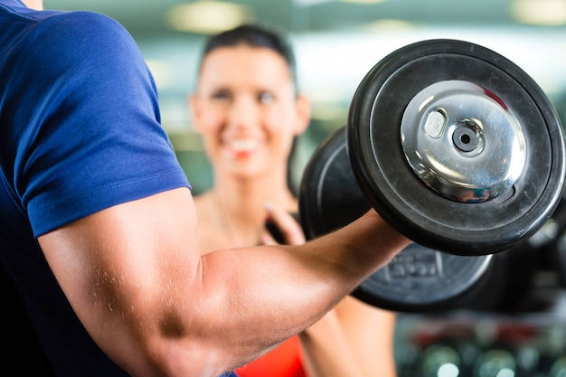 Personal trainer in palestra e allenamento con manubri