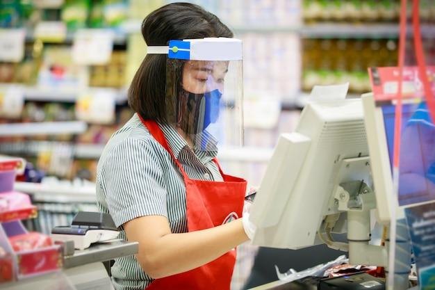 Personale del cassiere o del supermercato in maschera protettiva medica e visiera che lavora al supermercato.