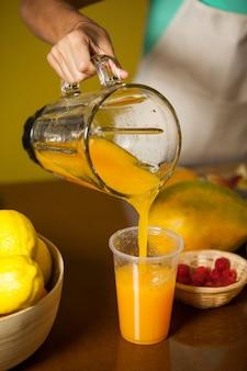 Personale femminile che versa il succo nel bicchiere al bancone