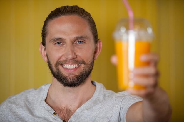 Personale maschio che tiene bicchiere di succo d'arancia alla sezione biologica