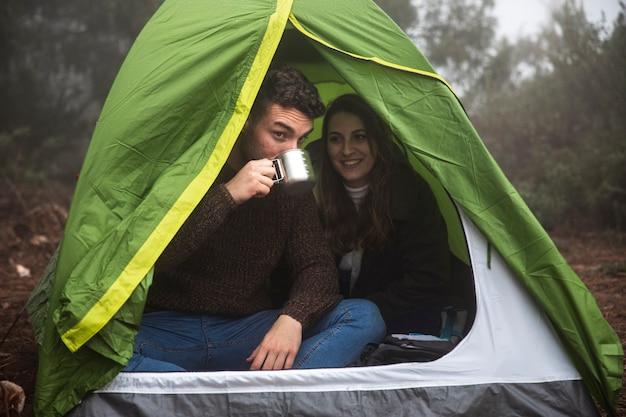 Persone a tutto campo che bevono in tenda