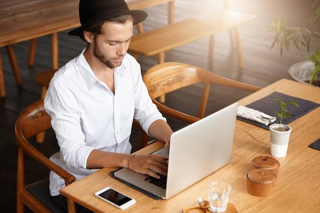 Persone, affari e concetto di tecnologia moderna. uomo alla moda in black hat tastiera sul laptop generico, utilizzando la connessione internet ad alta velocità, seduto al tavolo del caffè durante la pausa caffè