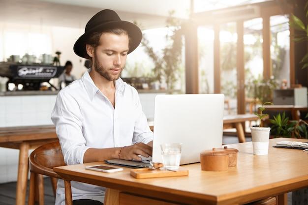 Persone, affari e tecnologia moderna. uomo bello serio e concentrato che si siede al tavolo del bar con bicchiere d'acqua e telefono cellulare durante la colazione, tenendo le mani sulla tastiera del suo laptop generico