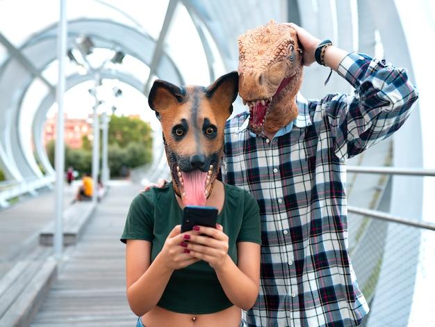 Persone alla moda coppia di moda indossando t-rex e maschera per cani