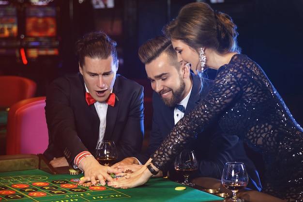 Persone belle e ricche che giocano alla roulette nel casinò