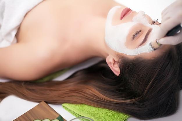 Persone, bellezza, spa, cosmetologia e cura della pelle - close up di bella giovane donna sdraiata con gli occhi chiusi e cosmetologo applicando la maschera facciale a pennello in spa