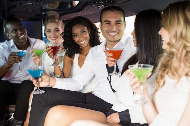 Persone ben vestite che bevono cocktail in una limousine