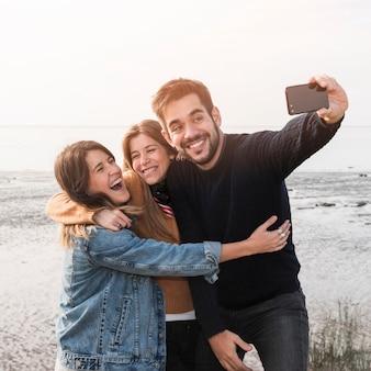 Persone che assumono selfie in riva al mare