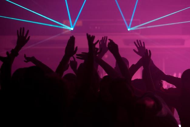 Persone che ballano nel club con il laser