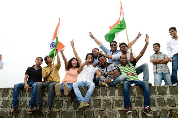 Persone che celebrano il giorno dell'indipendenza ballando e sventolando la bandiera indiana o il tricolore