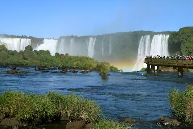Persone che esplorano le potenti cascate di iguazu con uno splendido arcobaleno dal lungomare, in brasile