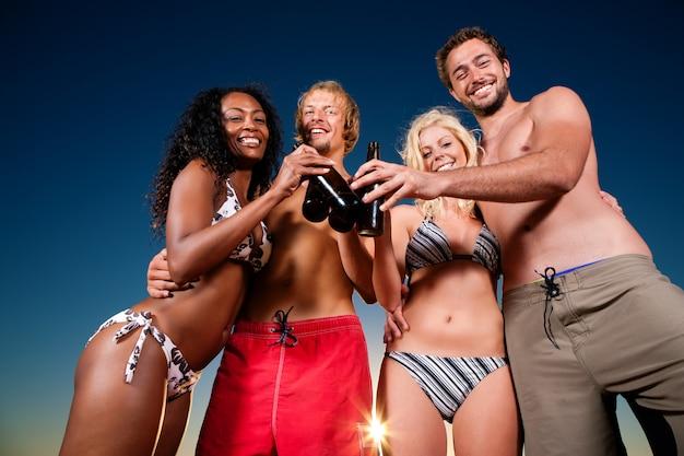 Persone che hanno festa in spiaggia con bevande