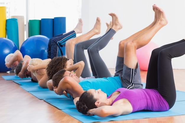 Persone che praticano yoga su stuoie di esercizio in palestra