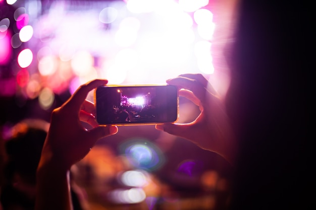 Persone che scattare fotografie con smart phone durante il concerto di musica dal vivo e folla