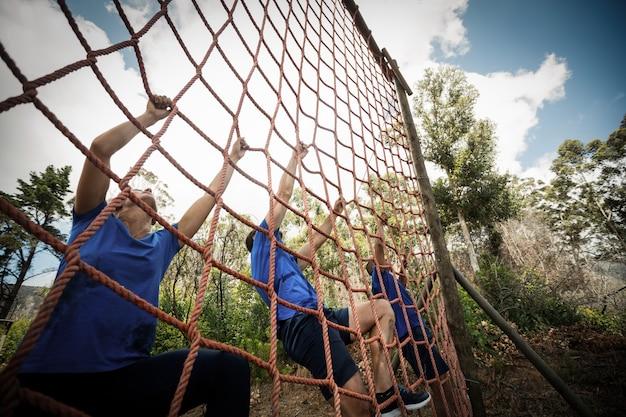 Persone che si arrampicano su una rete durante il percorso ad ostacoli