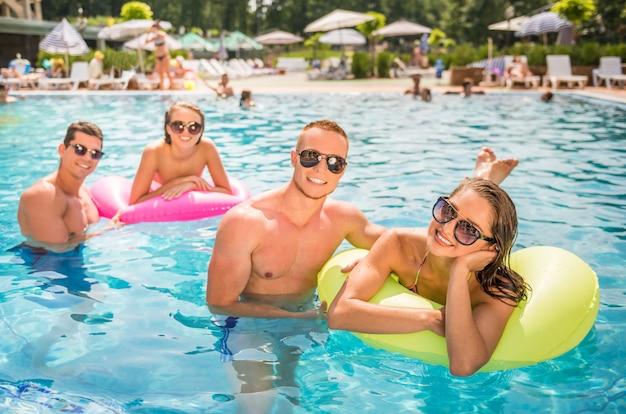 Persone che si divertono in piscina, sorridendo.