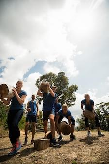 Persone che sollevano pesanti tronchi di legno durante il percorso ad ostacoli