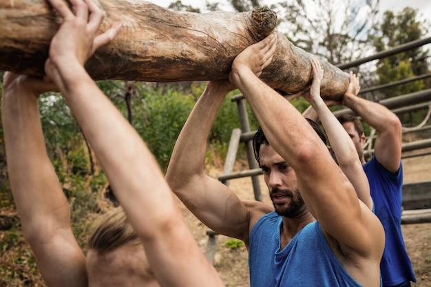Persone che sollevano un pesante tronco di legno durante il campo di addestramento