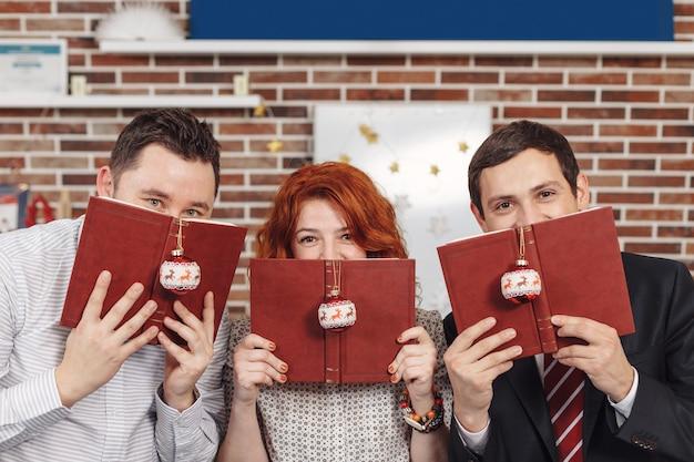 Persone che tengono i libri nelle mani mentre guardano al fac nascosto della macchina fotografica