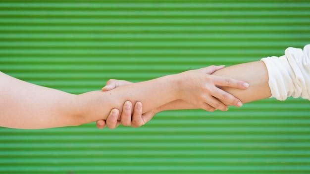 Persone che tengono le braccia