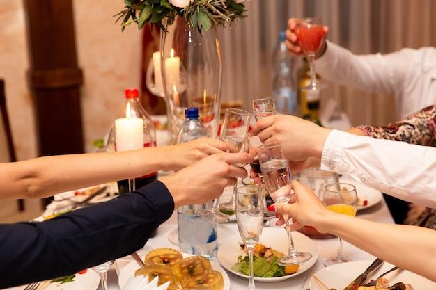 Persone che tostano bicchieri di champagne
