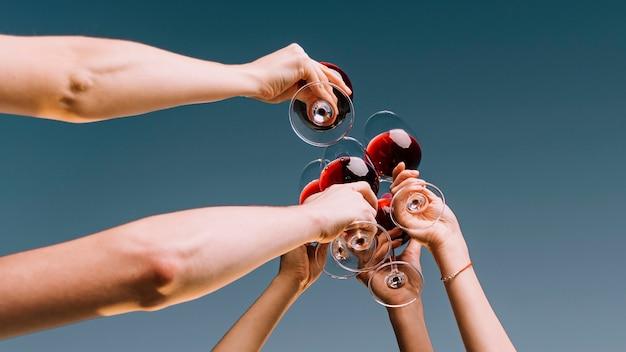 Persone che tostano il primo piano del vino dal basso