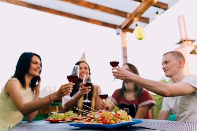 Persone che tostano vino alla festa