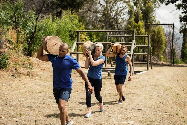 Persone che trasportano tronchi di legno pesanti durante il percorso ad ostacoli