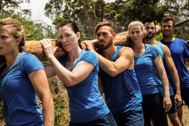 Persone che trasportano un pesante tronco di legno durante il campo di addestramento