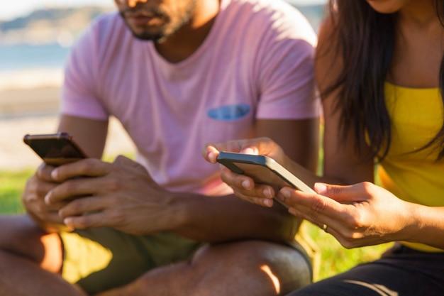 Persone che utilizzano i telefoni cellulari nel parco