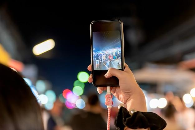 Persone che utilizzano telefoni cellulari fotografare i turisti nel mercato notturno