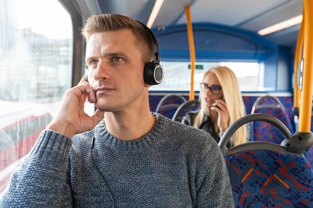 Persone che viaggiano in autobus a londra e mantengono le distanze sociali - uomo e donna che viaggiano su autobus vuoti in città e mantengono le distanze di sicurezza