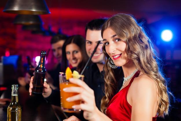 Persone con cocktail al bar o al club