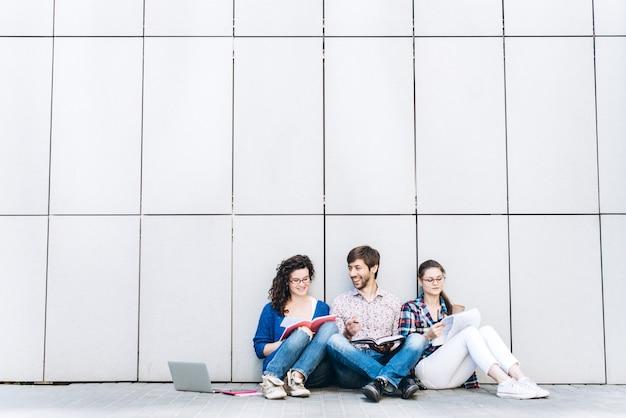 Persone con libri e gadget seduti sul pavimento vicino al muro. concetto di social media di educazione.