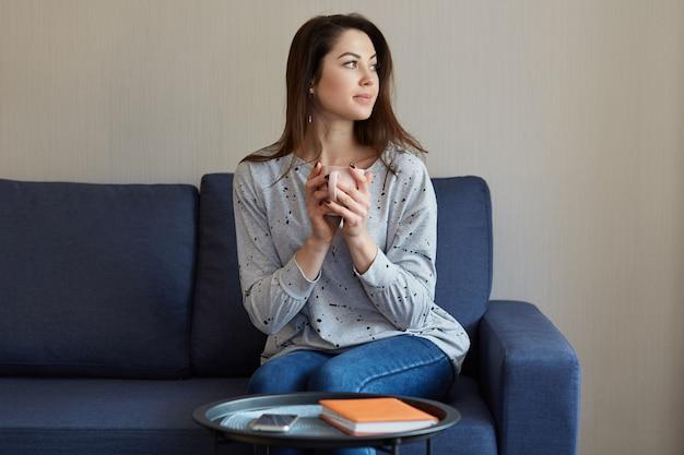 Persone, concetto di casa. la donna europea graziosa premurosa tiene la tazza della bevanda calda, vestita in maglione e jeans, si siede al sofà, messa a fuoco a parte, tavola rotonda con il telefono cellulare e blocco note rosso vicino