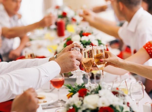 Persone dell'evento festivo che si incoraggiano a vicenda con lo champagne