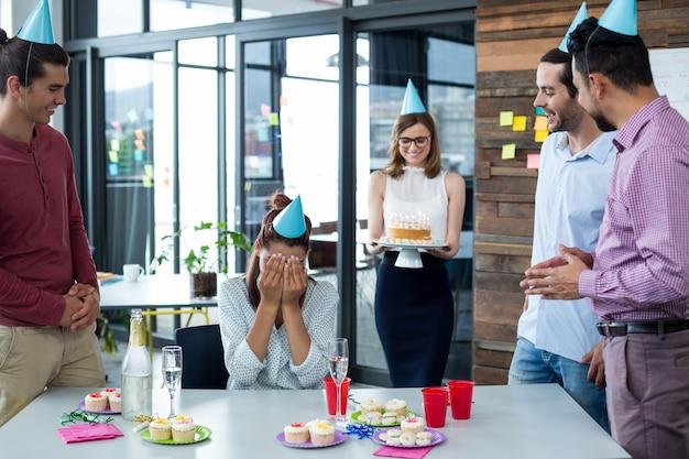 Persone di affari che danno la festa di compleanno di sorpresa al collega
