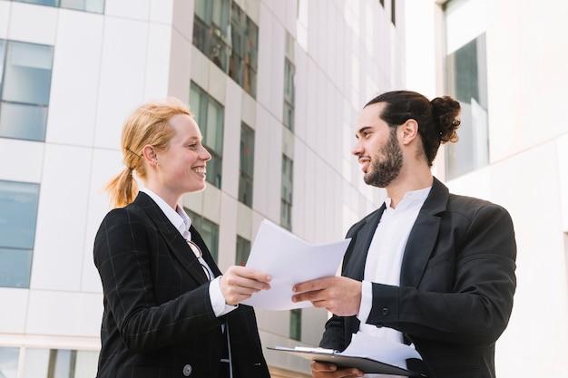 Persone di affari che stanno fuori l'edificio per uffici che tiene documento in mani