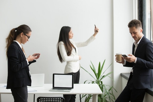 Persone di affari che usando gli smartphone che manda un sms, prendendo selfie nell'ufficio durante la pausa