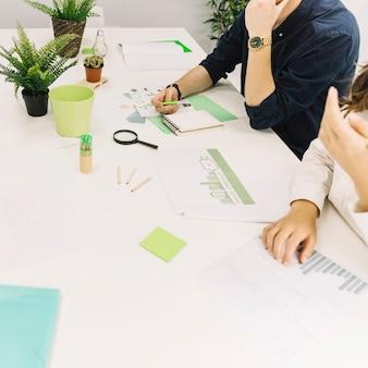 Persone di affari con il grafico e concetto di risparmio energetico su documento sopra lo scrittorio