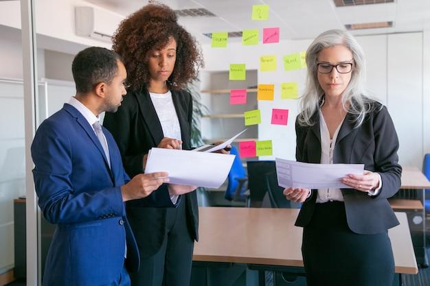 Persone di affari focalizzate che leggono documenti con statistiche. datori di lavoro di ufficio concentrati di successo in giacca e cravatta che si incontrano nella stanza dell'ufficio e studiano i rapporti. concetto di lavoro di squadra, affari e gestione