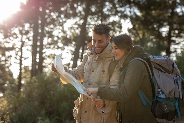Persone di tiro medio con mappa nella foresta
