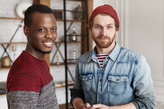 Persone e concetto di amicizia interrazziale. due vecchi amici maschi che si sono incontrati al caffè in piedi nell'interno del caffè moderno e conversando, entrambi con sorrisi felici