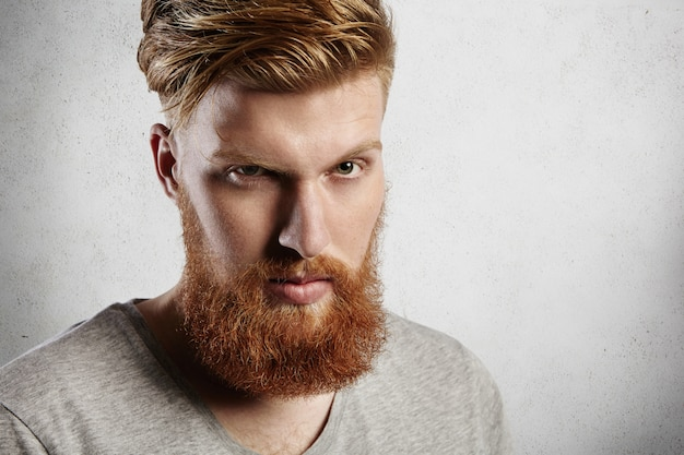 Persone e stile di vita. primo piano del volto di bei pantaloni a vita bassa con folta barba rossa e capelli alla moda con un'espressione seria del viso, socchiudendo gli occhi.
