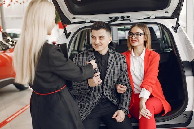 Persone eleganti e alla moda in un salone d'auto