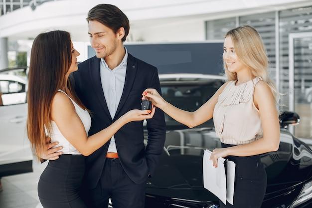Persone eleganti e alla moda in un salone di auto