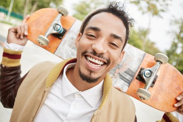 Persone, emozioni piacevoli, sentimenti e concetto di stile di vita attivo. contenuto adolescente di razza mista dalla pelle scura tiene lo skateboard,