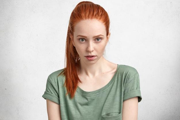 Persone, espressioni facciali e concetto di bellezza. attraente donna dai capelli rossi con la pelle lentigginosa, pensa a cosa fare oggi, guarda con sicurezza la telecamera, indossa una maglietta casual, isolata sul muro di cemento bianco